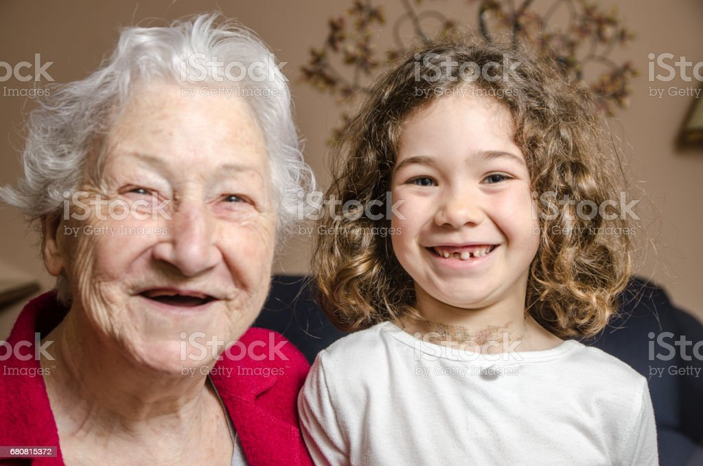 Grandmother and granddaughter both showing lack of teeth by smiling stock photo
