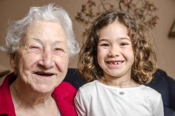 großmutter und enkelin anzeichen für fehlende zähne mit einem lächeln - zahnlücke stock-fotos und bilder