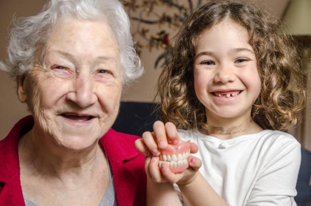 Grand-mère et petite-fille de deux montrant l'absence de dents en souriant - Photo
