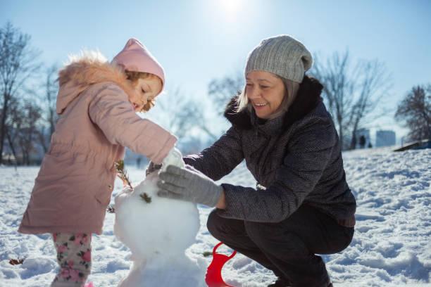 großmutter und enkelin beim schneemannbauen an einem wintertag - schneemann bauen stock-fotos und bilder