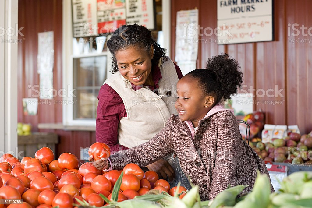 A grandmother and granddaughter choosing tomatoes stock photo