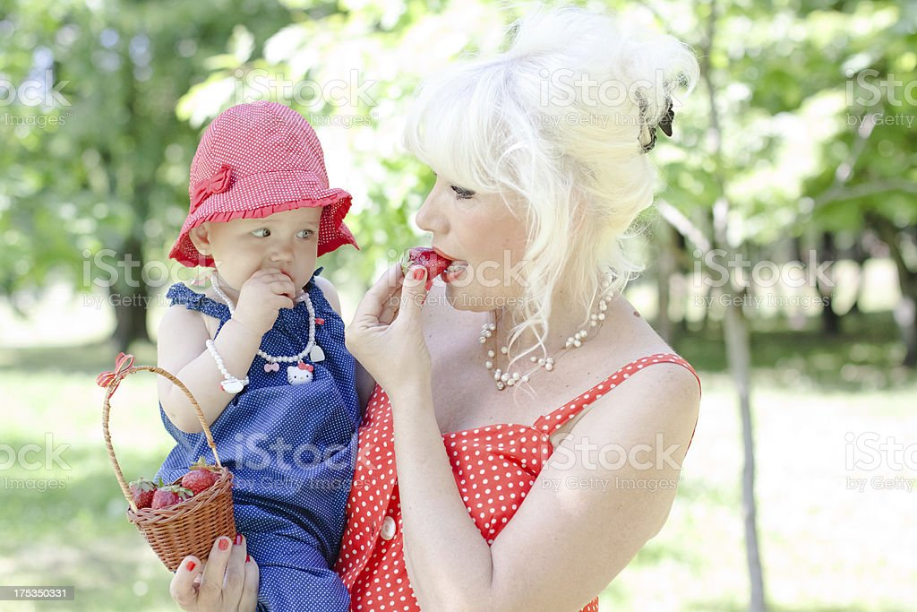 grandmother and granddaughter eating strawberries at the park royalty-free stock photo