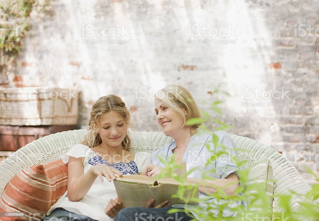 Grandmother and granddaughter enjoying book on patio royalty-free stock photo