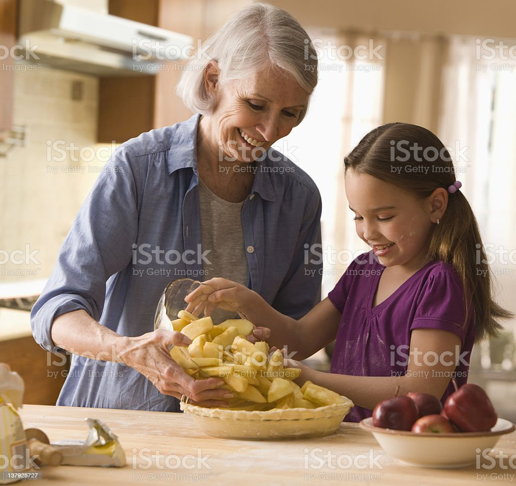 Grandmother and granddaughter filling in pie stock photo