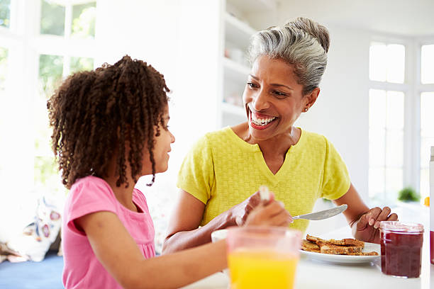 Grandmother And Granddaughter Having Breakfast Together stock photo