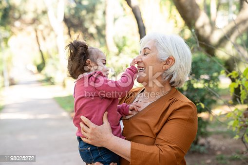 Senior grandmother holding her baby granddaughter in public park. Grandmother has white hair and is wearing an orange blouse. They are in outdoor. Selective focus on models. Shot with a full frame mirrorless camera.