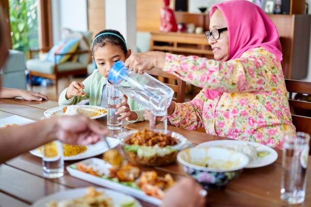 Grandmother and granddaughter having lunch at home stock photo