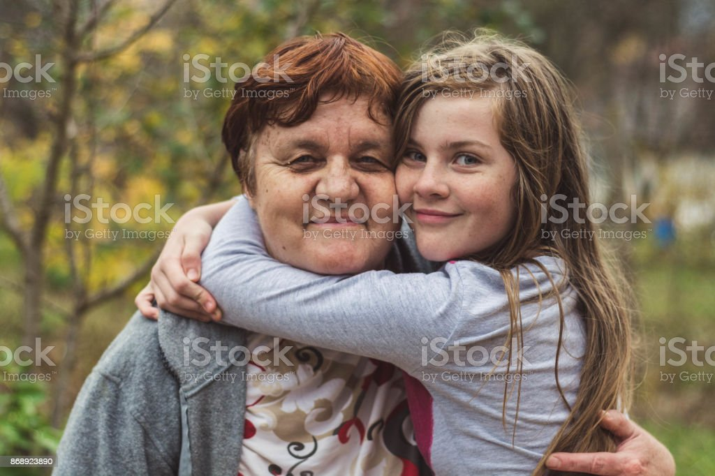 Grandmother and granddaughter hugging happily. stock photo