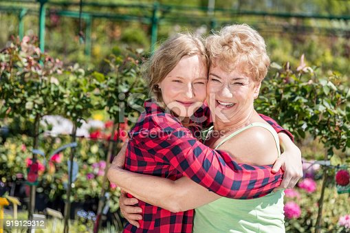 Grandmother and granddaughter embracing time together, hugging in a garden. Happy family