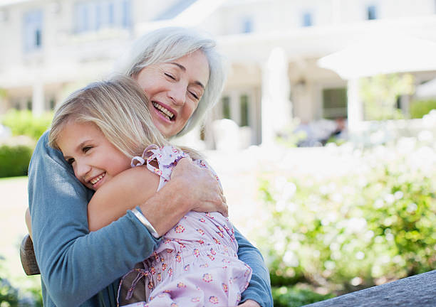 grandmother and granddaughter hugging in backyard - granddaughter and grandmother stock photos and pictures