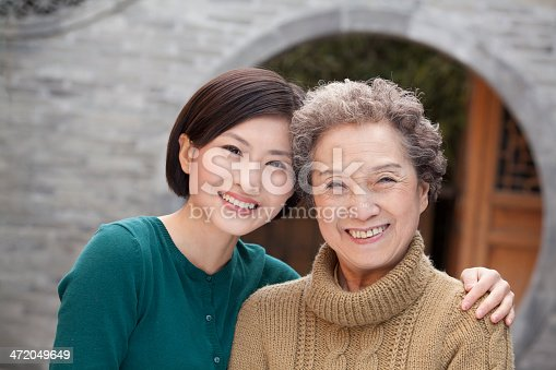 144362548istockphoto Grandmother and granddaughter in front of round arch, Beijing 472049649