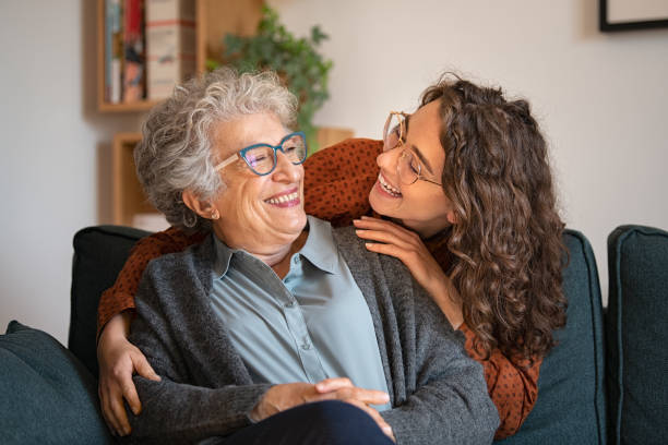 Grandmother and granddaughter laughing and embracing at home stock photo