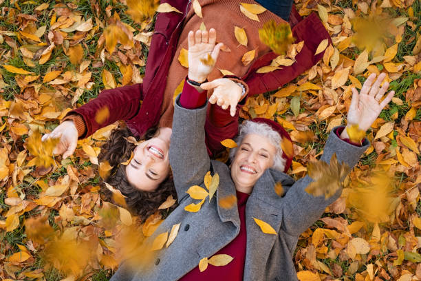 Grandmother and granddaughter lying on foliage and enjoy the autumn stock photo