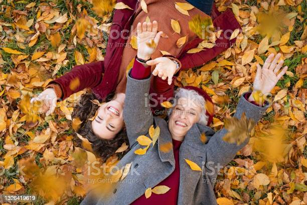 Photo of Grandmother and granddaughter lying on foliage and enjoy the autumn