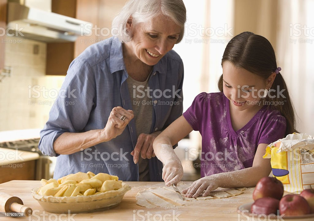 Grandmother and granddaughter making cover for pie stock photo