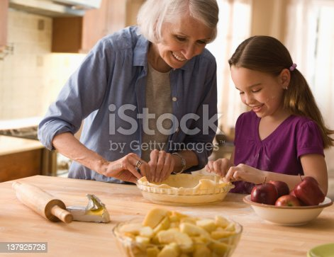istock Grandmother and granddaughter making pie crusts 137925726