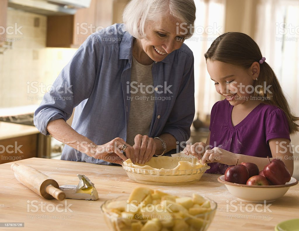Grandmother and granddaughter making pie crusts stock photo