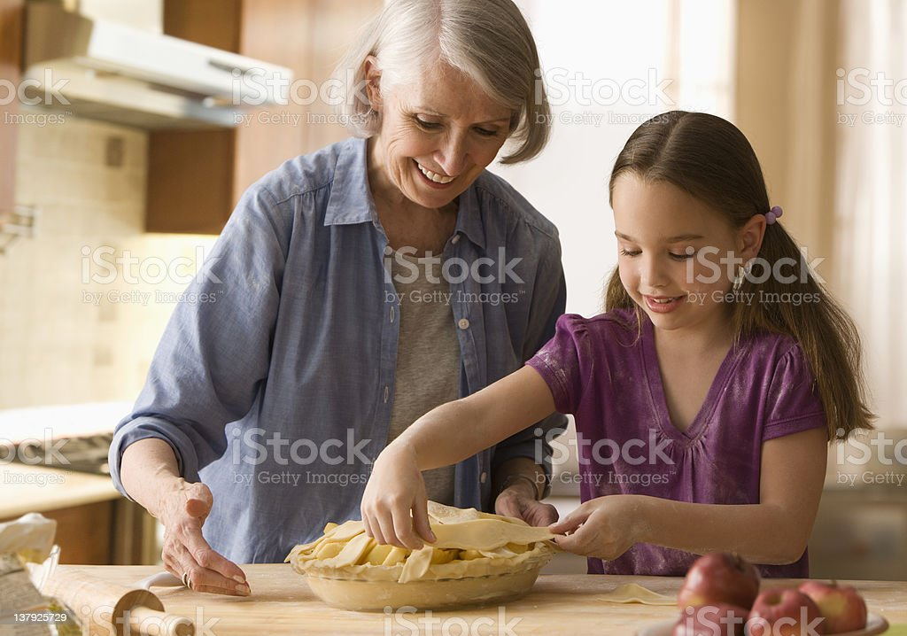 Grandmother and granddaughter making pie stock photo