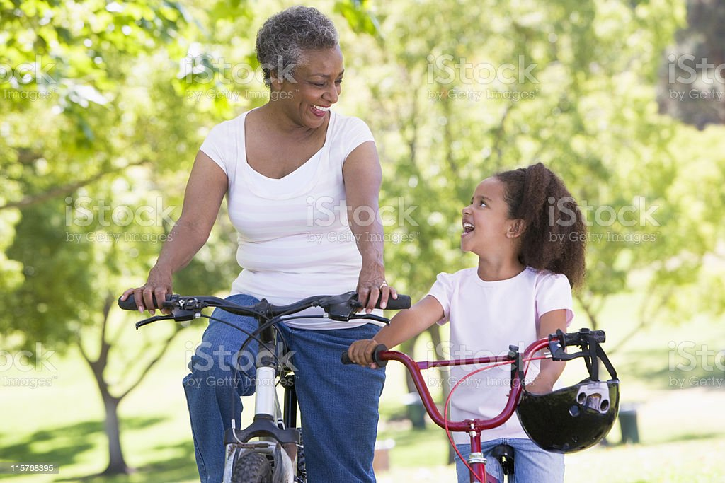 Grandmother and granddaughter on bikes outdoors smiling stock photo