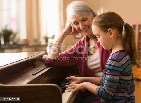 istock Grandmother and granddaughter  play piano 137925710