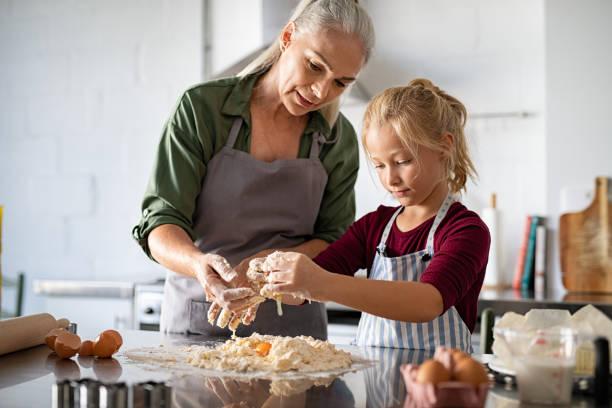 grandmother and granddaughter preparing dough - baking bread at home imagens e fotografias de stock