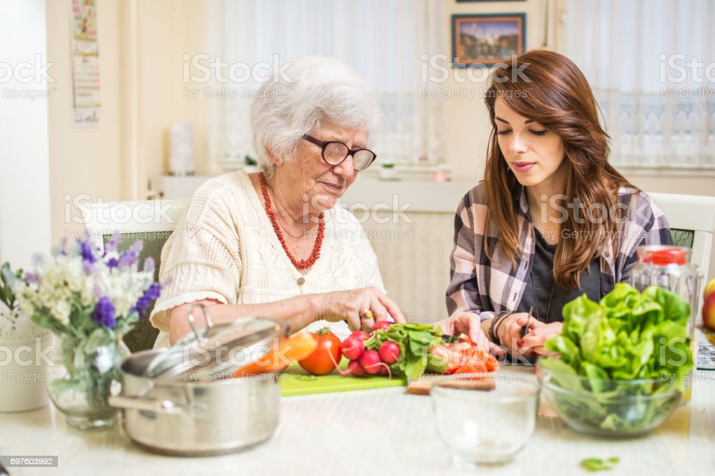 Grandmother and granddaughter preparing food together at kitchen. stock photo
