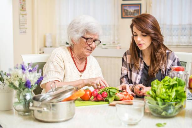 großmutter und enkelin, die zubereitung von speisen zusammen in der küche. - heimerziehung stock-fotos und bilder
