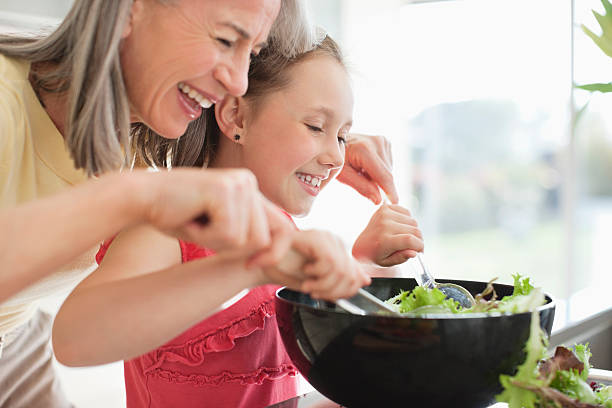 grandmother and granddaughter preparing salad - kids cooking stock photos and pictures