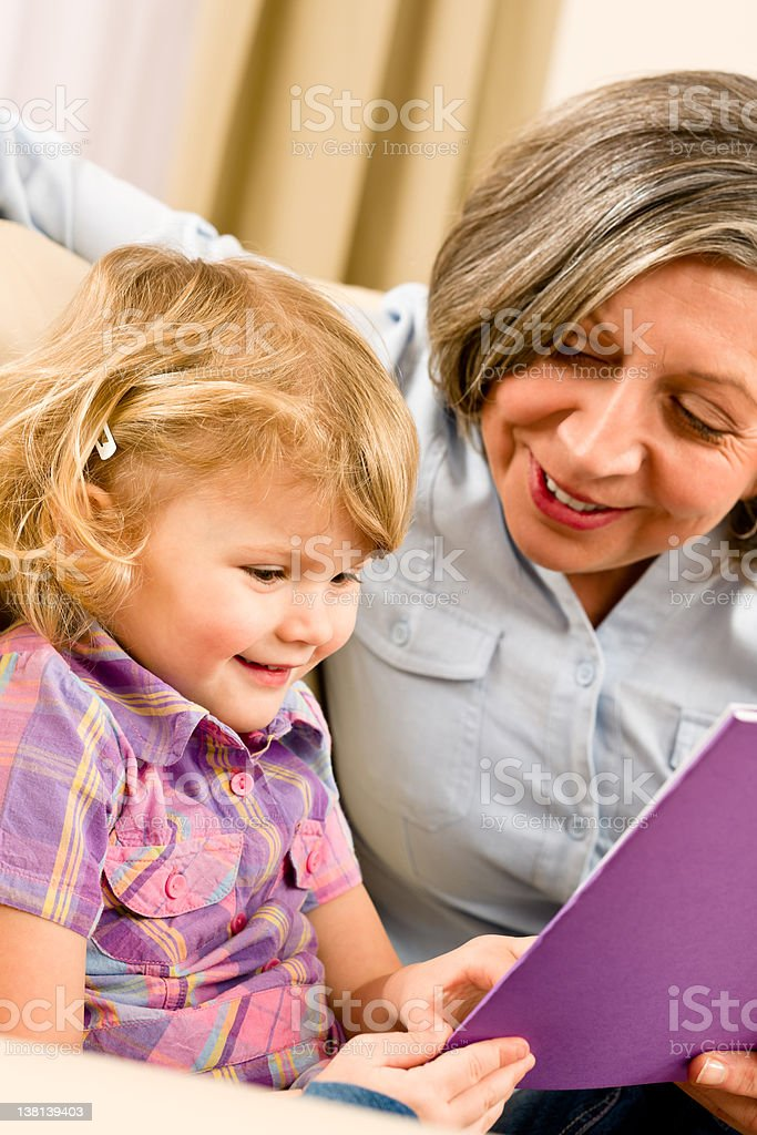 Grandmother and granddaughter read book together royalty-free stock photo
