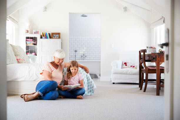 grandmother and granddaughter reading a book in her bedroom - granddaughter and grandmother stock photos and pictures