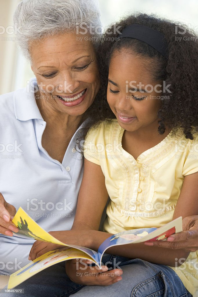 Grandmother and granddaughter reading whilst smiling stock photo