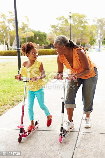 Grandmother And Granddaughter Riding Scooters In Park Smiling