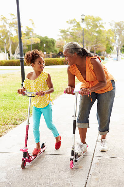 Grandmother And Granddaughter Riding Scooters In Park stock photo