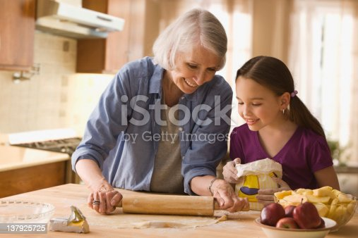 istock Grandmother and granddaughter rolling dough 137925725