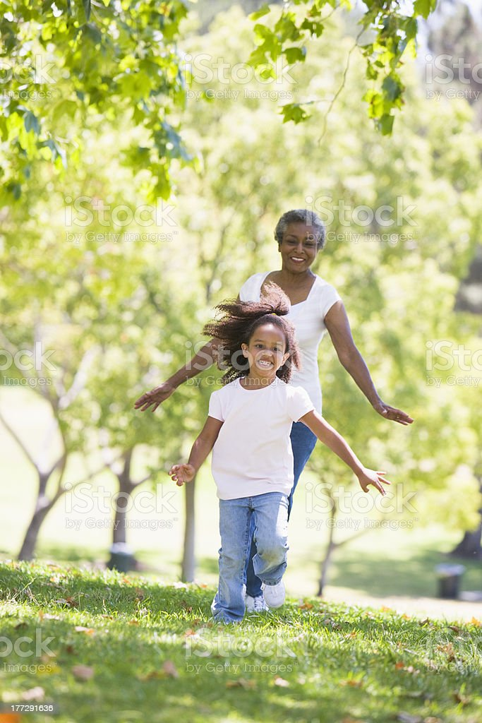 Grandmother and granddaughter running in park smiling stock photo