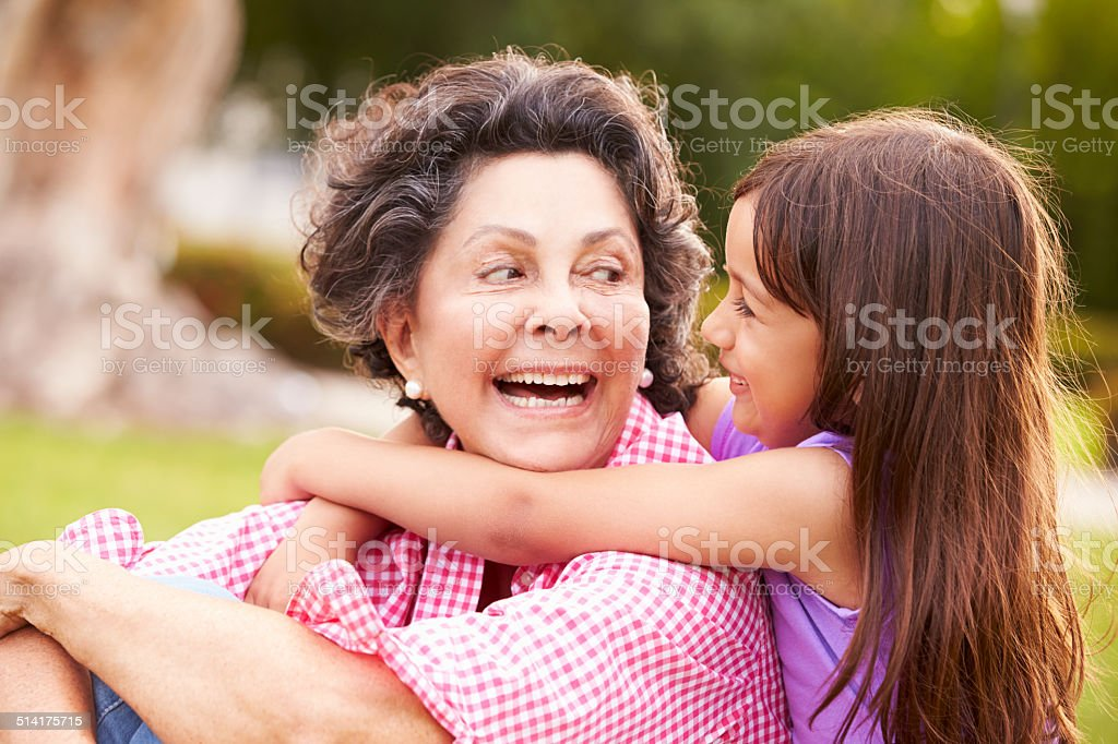 Grandmother And Granddaughter Sitting In Park Together stock photo