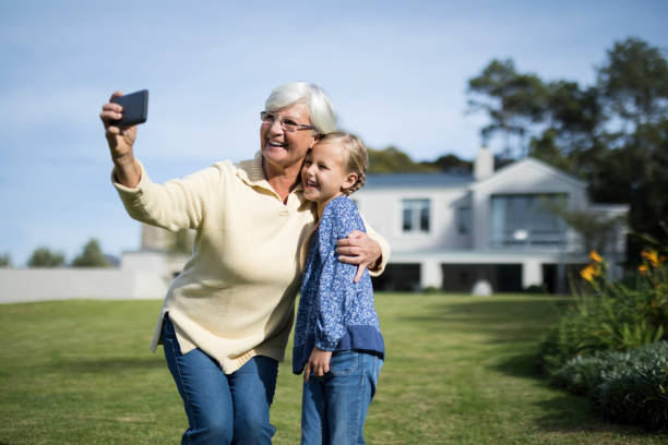 Grandmother and granddaughter taking selfie with mobile phone in garden stock photo
