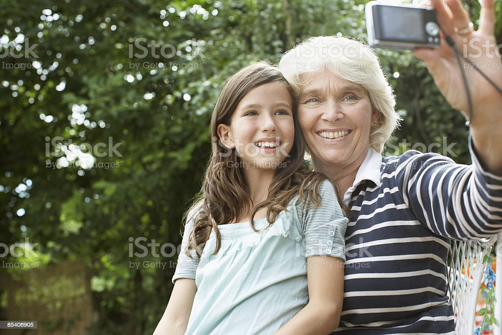 Grandmother and granddaughter taking self-portrait stock photo