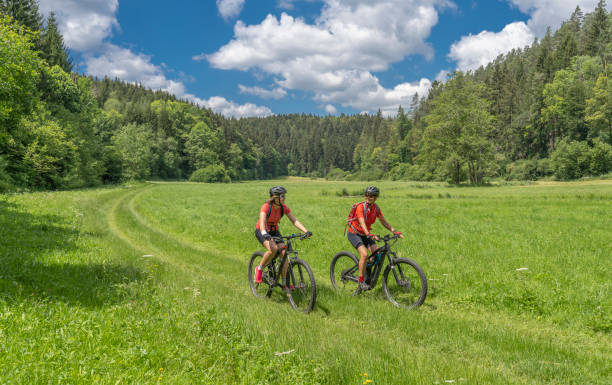 Grandmother and granddaughter with mountain bikes in Franconian Switzerland, Bavaria Grandmother with electric mountain bike and granddaughhter without electric help on a smooth meadow trail in the Franconian Switzerland area of Bavaria, Gemany electric bike tour stock pictures, royalty-free photos & images