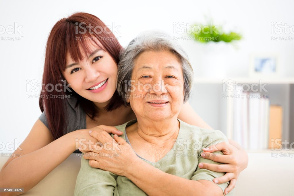 Grandmother and granddaughter. Young woman carefully takes care of old woman stock photo
