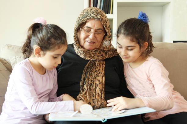 großmutter und granddaughters - storytelling fotos stock-fotos und bilder