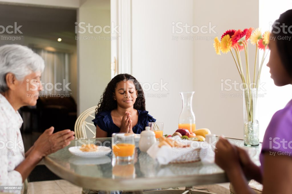 Grandmother and granddaughters sitting at table and praying - Royalty-free 12-13 Years Stock Photo