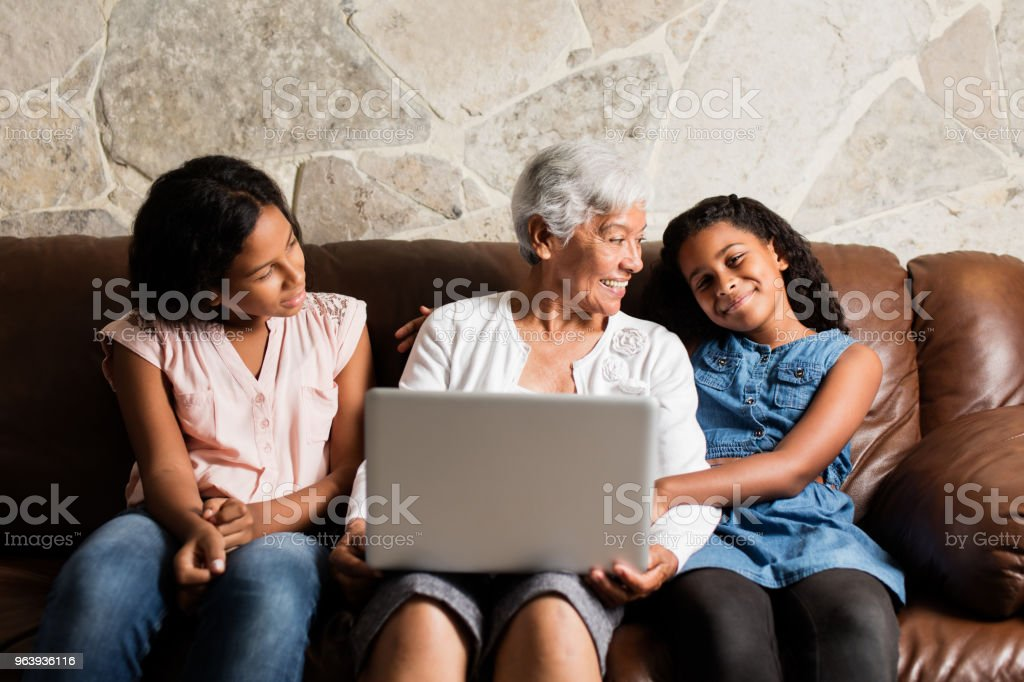 Grandmother and granddaughters sitting with laptop and smiling - Royalty-free 12-13 Years Stock Photo