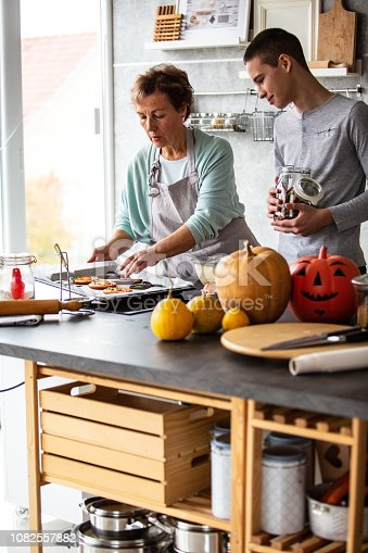 istock Grandmother and grandson baking cookies 1082557882