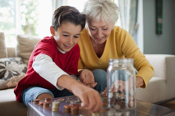 Grandmother and grandson counting coins stock photo