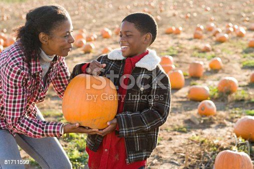81711567 istock photo A grandmother and grandson holding a pumpkin 81711599