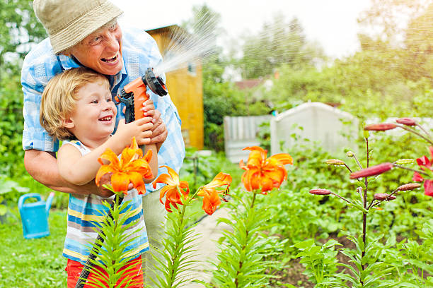 grandmother and grandson in the garden - garden hose stock pictures, royalty-free photos & images