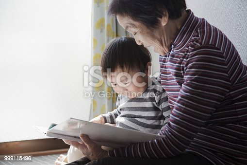 Japanese senior woman and her grandson reading a picture book at home.