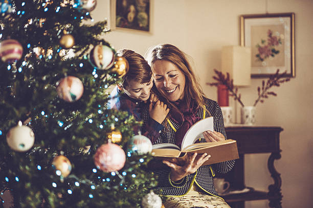 grandmother and grandson reading fairy tales on christmas - lustige weihnachtsgeschichte stock-fotos und bilder