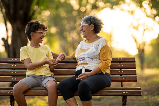 Grandmother and grandson are sitting in the park talking and smiling